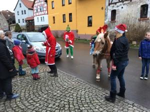 Weihnachtsmann und Weihnachtsgrinch mit Weihnachtspferd